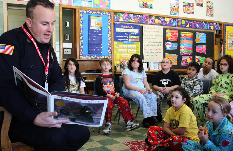 Lynn Police Officer Tim Donovan reads the Polar Express to a third grade class at the Sisson Elementary School in Lynn today. Photo by Owen O'Rourke