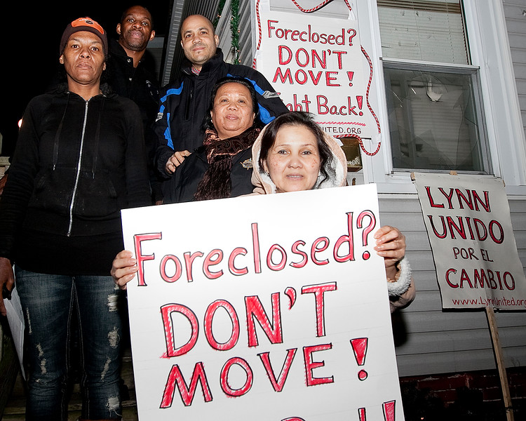 Tony Howard, Christino Acosta, Chana Seaforth, Chivvy Chum, and Diem Meang pose for a photo in front of Howard's home on Thursday, December 22. Howard was recently able to buy back his home after foreclosure with the help of Lynn United for Change. Item Photo / Angela Owens.