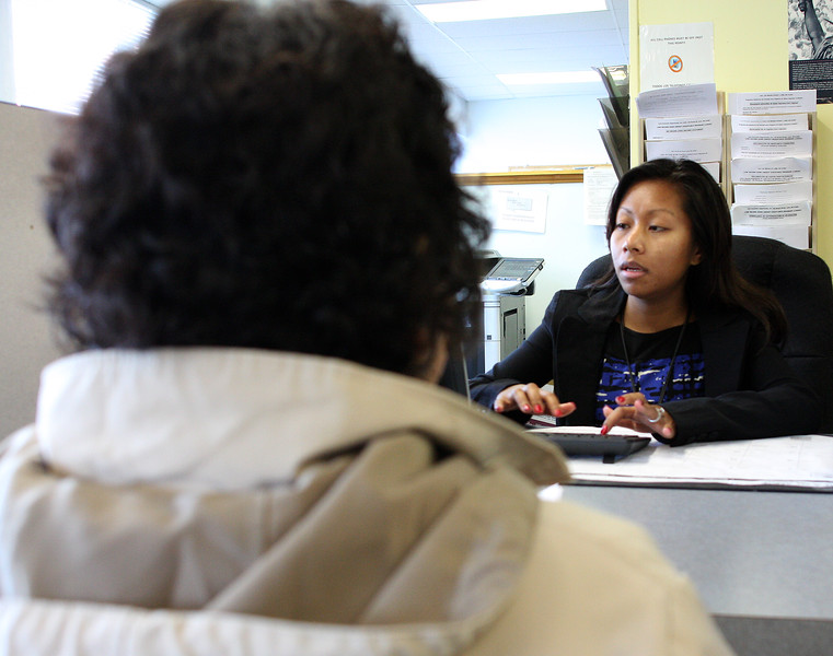 Lynna Chear, a bilingual advocate, helps a client with the fuel assistance program application process at the Lynn Economic Opportunity Office on Broad Street in Lynn. Photo by Owen O'Rourke