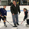 Al Donovan, middle, drops the puck for the faceoff to Alexander Cote, left of Canada, and Cayla Morrill of Lynn.