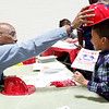 Ken Turner from the Lynn Fire Department gives a plastic helmet to Manuel Germosen, 8, at the Ingalls School resource fair on Tuesday, November 15. Item Photo / Angela Owens.