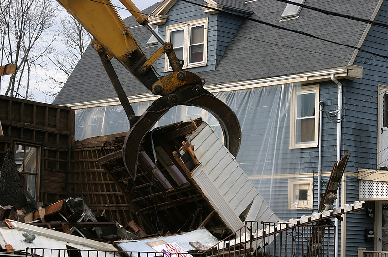 A demolition crew taking down a church on Burrill Street hung plastic over a neighboring building to prevent the church's slate roof from falling and potentially breaking windows.