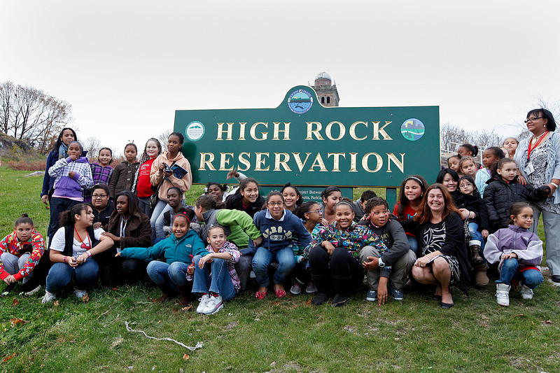 Mayor Judith Flanagan Kennedy poses for a photo with girls from Girls Inc in front of the recently unveiled High Rock Reservation sign on Tuesday, November 15. Item Photo / Angela Owens.
