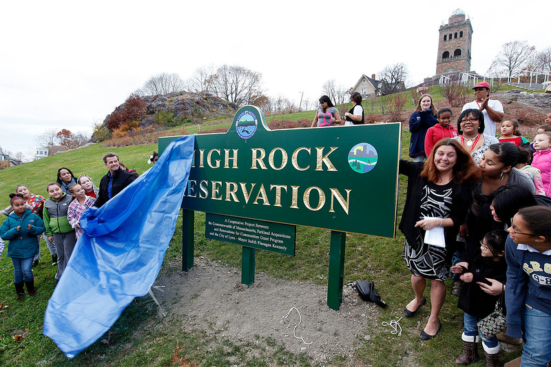 Michael Murray from the Department of Community Development and Mayor Judith Flanagan Kennedy, surrounded by girls from Girls Inc, unveil the new sign at the High Rock Reservation on Tuesday, November 15. Item Photo / Angela Owens.