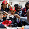 Ken Turner from the Lynn Fire Department hands out plastic helmets and information to Christopher Runyon, 5, Jessica Delosantos, age 11, and Manuel Germosen, 8, at the Ingalls School resource fair on Tuesday, November 15. Item Photo / Angela Owens.