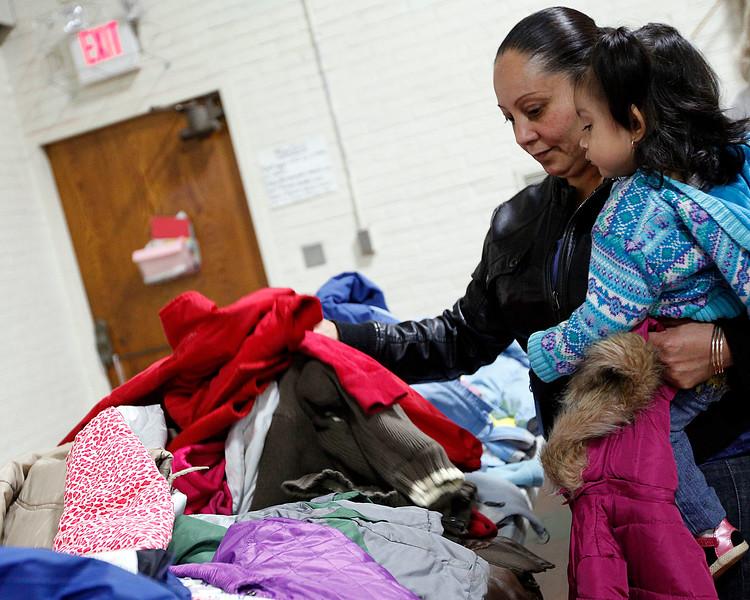 Evalia Perez, with her daughter Berani Perez, looks through the $1 coat sale at the Ingalls School resource fair on Tuesday, November 15. Item Photo / Angela Owens.