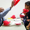 Ken Turner from the Lynn Fire Department hands out plastic helmets and information to Jessica Delosantos, age 11, and Manuel Germosen, 8, at the Ingalls School resource fair on Tuesday, November 15. Item Photo / Angela Owens.