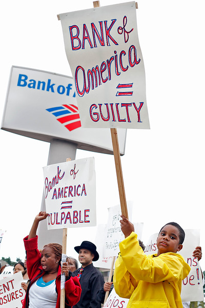 Rosalina Alcantara, left, and Wilkin Frias, age 9, right, hold signs and protest with a group called Lynn United for Change, outside the Bank of America on Market St in Lynn on Thursday, September 22, 2011. By Angela Owens.