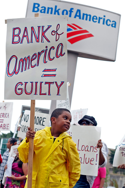 """Wilkin Frias, age 9, holds a sign stating """"Bank of America = Guilty"""" during a protest with Lynn United for Change outside the Bank of America on Market St in Lynn on Thursday, September 22, 2011. By Angela Owens."""