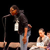Item Regional Spelling Bee. Lynn City Hall Auditorium.  #24 Victoria Kadiri, grade 8 at Kipp Academy, Lynn, spells a word in the competition. Seated are #20 Celeste Bucci grade 8 of Holten-Richmond Middle School, Danvers and #19 Sofia Valencia, grade 6 of Higgins Middle School, Peabody.
