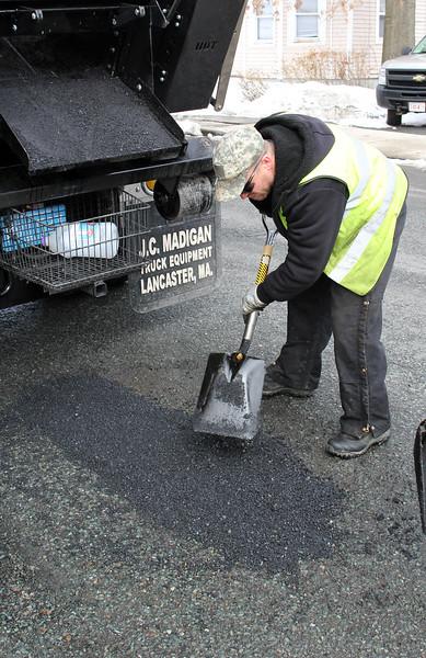 Erick Kneeland fizing a pothole on Myrtle Street in Lynn. Photo by Owen O'Rourke