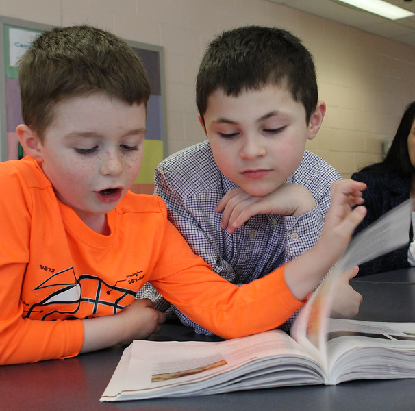 Joey Piazza, left, and Cayden Alvarado, right, flipping through the book Minecraft during the Campfire Northshore's Absolutely Incredible Kid Week at the Shoemaker Elementary School today. Photo by Owen O'Rourke
