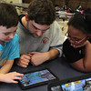 Brady Cole, left, Connor Doliber, middle, a counsilor, and Tianna Burton, right, build bridges on a tablet at the Absolutely Incredible Kid Day at the Shoemaker Elementary Schoo. Photo by Owen O'Rourke