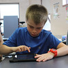 Ian Brown works on a tablet during the Camp Fire North Shore Absolutely Incredible Kid Day at the Shoemaker Elementary School in Lynn. Photo by Owen O'Rokurke