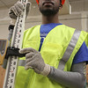 Dalvin Howard, a student at Lynn Vocational Technical Institute, with a grade rod, a tool usen in surveying, during classes held by the New England Labrorer's Union this week. Photo by Owen O'Rourke