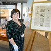 Lynn, Lynn Musuem.  Nicole Breault, Lynn, Educational Programs Coordinator, with a front page of  The Saturday Union,  a Lynn paper.  This page diplays designs for women's shoes and dates Oct 3, 1885.