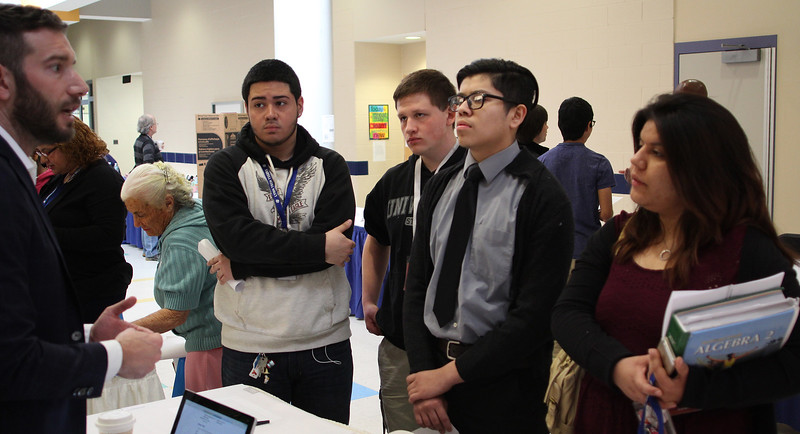 Stephen Arena, left, of Autobody Clinic, collision repair North Shore, tells Luis Ayala, George Papageorgiou, Rafael Marroquin and Tania Ortiz, all students at Lynn Vocational Technical Institute, about the profession at the job fair today. Photo by Owen O'Rourke