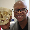 Kevin Gomes, a senior at Lynn Vocational Technical Institute who wants to major in biology in college, poses with a skull from the Partners Health Care of North Shore table at the job fair held at Tech today. Photo by Owen O'Rourke
