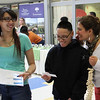 Aliana Colon, left, and Pamela Norm, middle, both seniors at Lynn Vocational Technical Institute, get some heip from Banafsheh Salamat, a teacher at Tech, on a health question regarding bones in the human ear at the Partners Health Care North Shore table at the job fair at Tech today. Photo by Owen O'Rourke