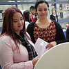 Deja Albee, left, and Savanny Kent, right, both seniors at Lynn Vocational Technical Institute, spin the wheel to win a prize at the Cher Magic hair counter at the job fair at Lynn Vocational Technical Institute today. Photo by Owen O'Rourke