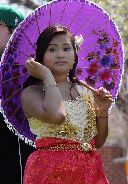 Sokhema Chhorn waits to perform on stage as a brides maid at the Cambodian New Year celebrations held on Lynn Common Saturday. hoto by Owen O'Rourke