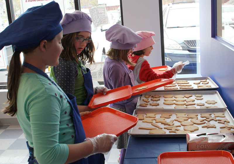 Katherine Ducharme, left, Grace Mann, Lauren Ballou and Emily Fulton choose their cookies at the start of cookie decorating class today at Cygnet on Lynnfield Street in Peabody. Cygnet offers classes in cake decorating classes, cupcake wars, birthday parties, and a girl's night out event Tuesday through Sunday. Photo by Owen O'Rourke