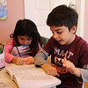 Home schooled children Nicole, left and Kyle Costa, right, working at their desk adjacent to their livingroom in Lynn. Photo by Owen O'Rourke