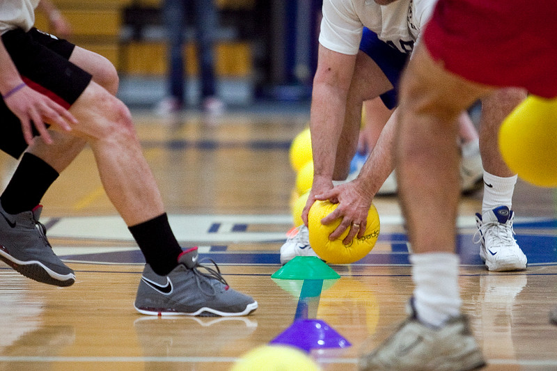 The Soccer Dads and Stanley Dodgers race to collect the balls at the start of their game in the dodgeball tournament at Swampscott High School on Wednesday, April 4. Item Photo / Angela Owens.