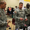 Bronson Cambra, Ethan Schweitzer, and Kenneth Okello from the United States Army had a table at the job fair for veterans and the community at North Shore Community College in Lynn today. Photo by Owen O'Rourke