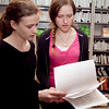 Kiely Quinn, 15, and her sister Ashling Quinn, 17, look over the schedule for the TV production class annual auction at Swampscott High School on Tuesday, May 6. Item Photo / Angela Owens.