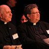 Father Gregory Mercurio, St. Pius V Pastor, left, and Father Brian Flynn, St. Mary's & Sacred Heart Collaborative Pastor, right, during the Lynn Catholic Schools partnership assembly in the auditorium at Lynn City Hall today. Photo by Owen O'Rourke