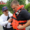 Lynn Fire Captain Jay Uva, left, helps Lynn Fire Fighter Joe Comeau, right, secure his life jacket prior to his going out on Sluice Pond in the 12 foot inflatable belonging to engine 10 today. Photo by Owen O'Rourke