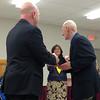 Brant Duncan, president of the Lynn Teachers Union local 1037, hands a gift to retiring teacher Ronald Bennett at the school administration building on Thursday, June 12. Item Photo / Angela Owens.