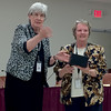 Superintendent Dr. Catherine Latham presents a gift to retiring principal Bernadette Stamm at the school administration building on Thursday, June 12. Item Photo / Angela Owens.