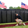 Bruce Dobson, of the Vietnam Veterans of America 908, points to the name of a soldier from Revere who was killed in Vietnam on the Wall That Heals now on display through Sunday at the Bennington VFW Post 6712. Photo by Owen O'Rourke .
