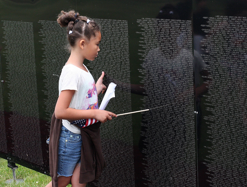 Nailah Brown, a third grade student at the Beachmont Veterans Memorial School in Revere, looks at the Wall That Heals containing the names of all of the soldiers killed in Vietnam, the youngest being 15 years old. The wall is on display at the Bennington VFW Post 6712 in Revere through Sunday. Photo by Owen O'Rourke .