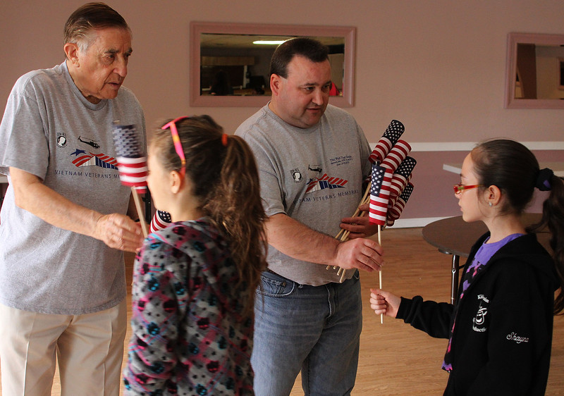 Len Piazza, left, and Rick Labadini, right, hand out flags to a fifth grade class from the Beachmont Veterans Memorial School in Revere as they headed out to see the Wall That Heals. The wall, loacted at the Bennington VFW Post 6712 in Revere, will be open to the public through Sunday. Photo by Owen O'Rourke