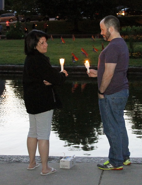 Diane Giambrone and Steven Mahoney hold lighted candles at the edge of Goldfish Pond.