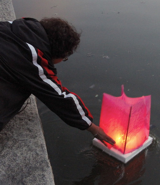 Launching a floating candle covered in pink. Candles of different were sent into all areas of the pond.