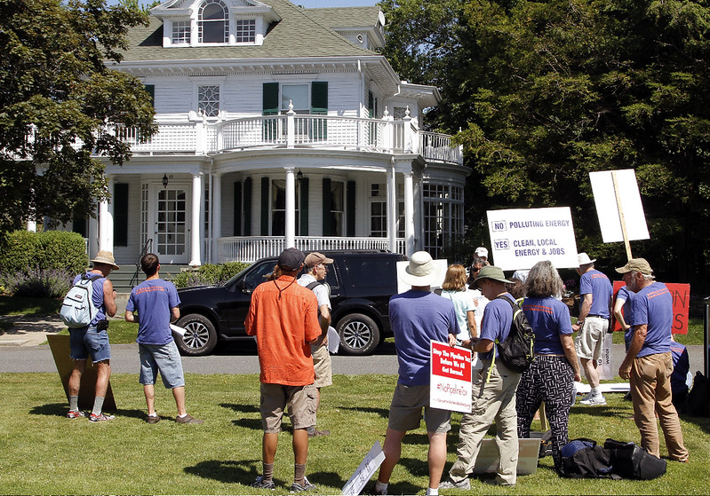 A group of about 30 people gathered on the grass across from Governor Baker's house to protest pipelines and global warming.
