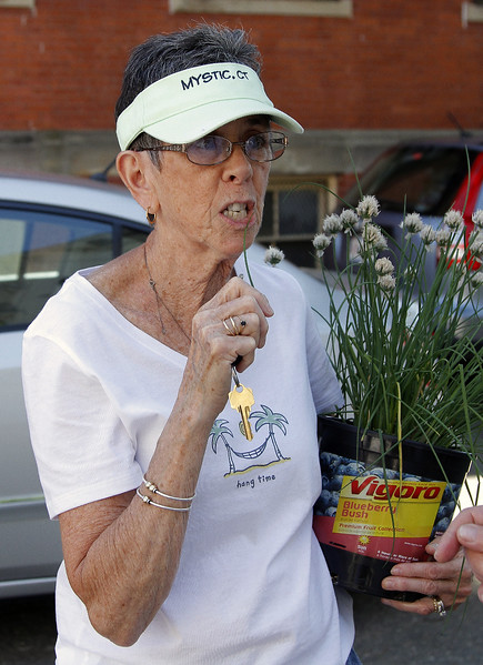 Susan Hobbs samples a sprig of chive from her plant.