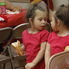 Two year old Aundrea Pasquerello is moving chairs while her three year old sister, Ariana, has found a twin.