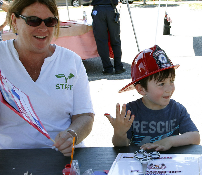 Mary Webster helps four year old Lucas Hutchings paint his hand red, white and blue.