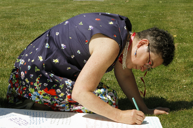 Andrea Doremus adds her name and a petition to a card presented to Governor Baker.