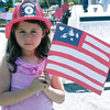 Siena Postizzi wears a fireman's hat and waves a flag that she made.