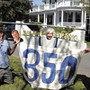 Carolyn Britt from Ipswich puts her head on the 350 sign held by Fred Hoppe and Patrick Patterson.