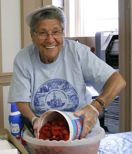 Margie Berkowitch adds another tub of strawberries for her shortcakes.