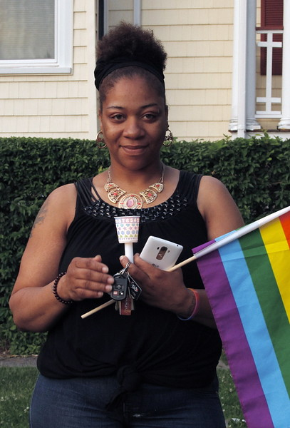 Nellie Foy carries a rainbow flag as well as a lighted candle.
