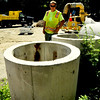 "Swampscott. ""The Pad"" at Swampscott Cemetery. Steve Alex, Beverly, a DPW worker, looks at the catch basins that are going to be used for fire pits on the beach in Swampscott.  Several are mini catch basins."