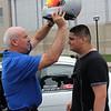 Steve Hazard from Universal Technical Institute, puts a $1,100 racing helment on Gerson Estrada, a member of Camp Bulldog at Lynn English High School. Photo by Owen O'Rourke